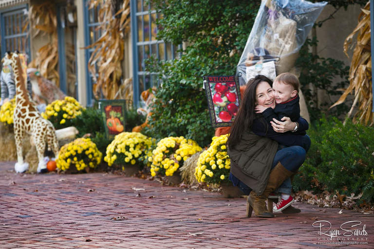 Peddler's Village Family Portrait Session - A loving mother hugs her first born sun in front of cute fall decorations at Peddler's Village.