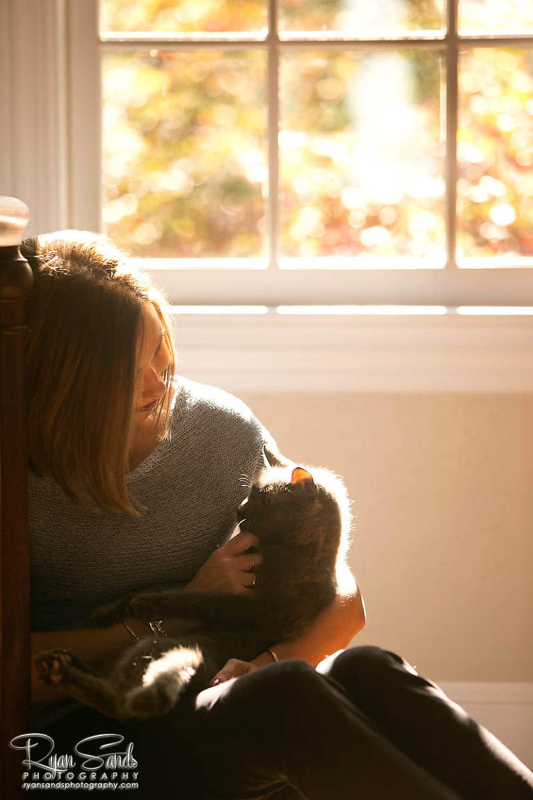 Newtown PA Photographer - As she sits with her loving cat the sun beats down on them from a window behind them.