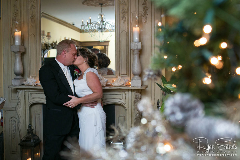 Gables Inn Wedding - The inn was decorated for Christmas with lights, wreaths and much more. Here the bride and groom share a kiss near the fireplace.