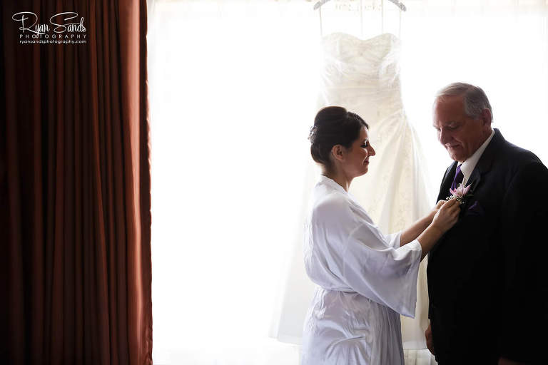 A Forsgate Country Club wedding is a special day. Here Lisa pins her father's wedding boutonniere on his jacket in front of a large window.