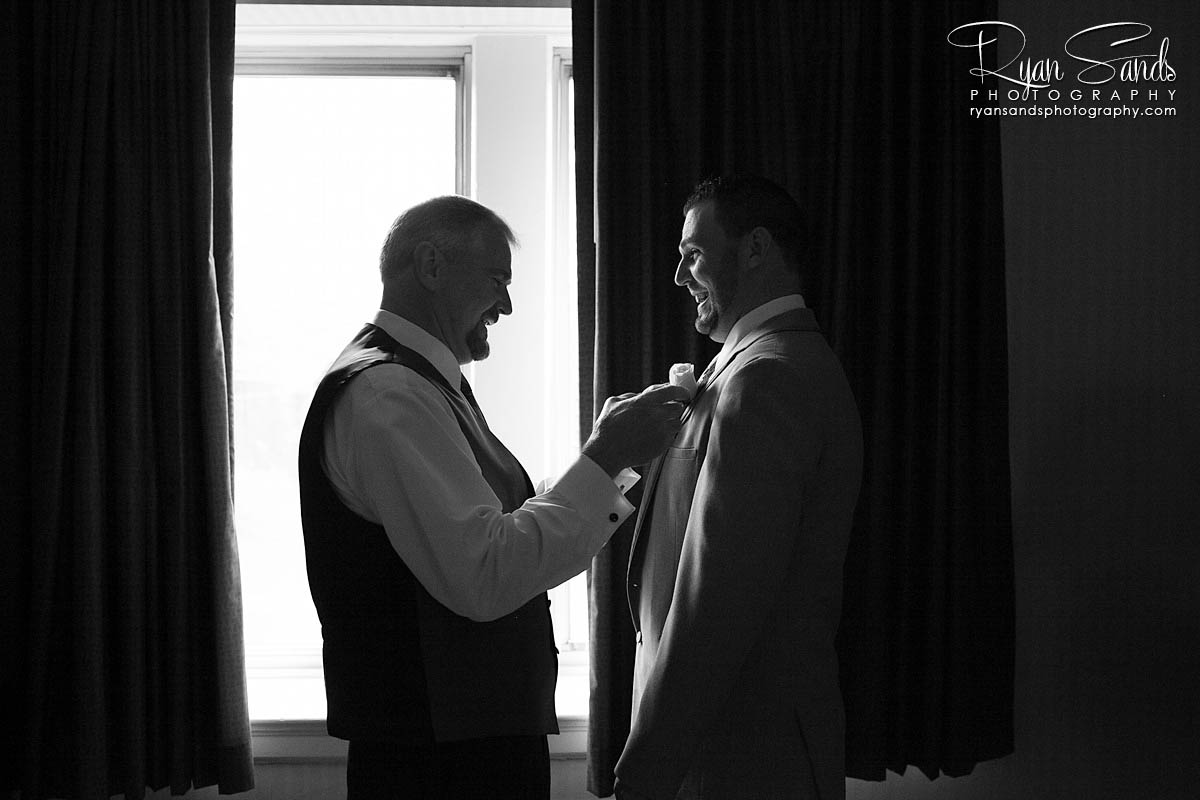 Grand Summit Hotel Wedding - Here you can see the groom standing in front of a large window having his flower pinned on his jacket on the morning of his wedding day.